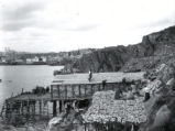 (03 07 006) The Battery, St. John's. Women working on flakes, drying fish, with St. John's in the...