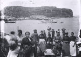 29.01.017: Newfoundland community, unidentified. Group of people standing on the shore with...