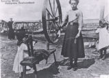 "(32 03 001) Conception Bay. ""Spinning Wheel, Kelligrews, Newfoundland,"" showing a young girl using a"