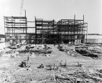 082 Photo of steel erection in third stage looking east. Part of library on right covered with...