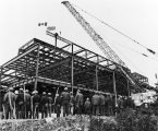 129 Workers watching the last piece of steel set in place. Also witnessing the ceremony were the...