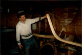 Patrick Lainey holding a pair of cut timbers forming bottom frame of boat