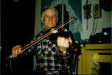 Émile Benoit plays the fiddle at his home in Black Duck Brook