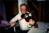Émile Benoit playing the fiddle at his home