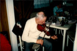 Émile Benoit playing the fiddle in his kitchen