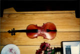 Photo of 100-year-old fiddle [at time of photo] on the wall at Émile Benoit's house