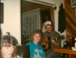 Gerry Benoit playing the guitar for two visiting folklore students, Helen and Shirley