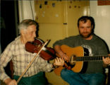 Émile Benoit playing fiddle with his son Gerry on the guitar, entertaining the folklore students...