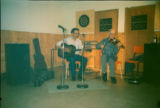 Émile Benoit playing the fiddle and Howard Oliver playing the guitar at a talent show at the...
