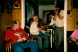 Émile Benoit playing the fiddle with Gerald Thomas playing the mouth organ at a party at Émile...