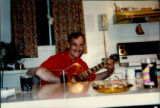 Party at Émile Benoit's house. Gordon Benoit playing the guitar