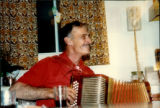 Party at Émile Benoit's house. Gordon Benoit playing the accordion