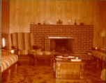 View of the Sheppards' living room showing the fireplace, chesterfield set, carpet, tables, etc