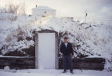 Man standing in front of root cellar