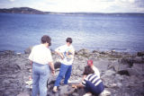 People having a boil up on rocky beach