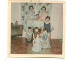 Cantwell, Theresa Squires. Colour photograph of two women, a man, and five children in living room...