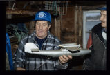 Len Brown in his store with a wooden model airplane, Joe Batt's Arm