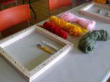Materials for making pillow tops. Wooden frame, small twine needle, fishing twine and wool of...
