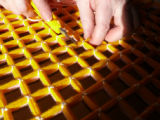 Cutting the wool to form pom poms on the top of the pillow top.