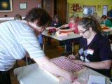 Elizabeth Murphy shows Jenny Tarof how to weave a pillow top.
