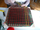 A pillow top in progress, with several layers of wool woven on the frame.