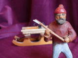 Wooden carving of lumberman with axe and model of a sled carrying a load of logs, Botwood