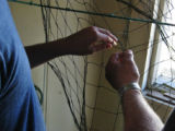 "Alphonsus ""Phonse"" Ducey showing Edward Millar how to mend a fishing net"