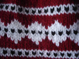 Patey, Karen H.  Close-up of a red and white winter hat made by Karen Patey, Quripon.