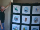 Reid, Marie and Oliver.  Oliver holding up a painted Newfoundland quilt made by Marie Reid,...