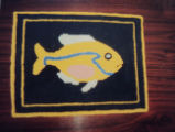 Wells, Dale.  A fish themed hooked mat coaster made by Dale Wells, St. Anthony.