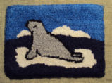 Wells, Dale.  A seal themed hooked mat coaster made by Dale Wells, St. Anthony.