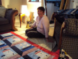 Wells, Dale.  Dale Wells posing with a quilt in her living room, St. Anthony.