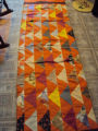Tucker, Clara.  An orange triangle motif quilt made by Clara Tucker, St. Anthony.
