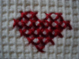 Tucker, Clara.  Close-up of a cross-stitched heart on a chair cover made by Clara Tucker, St....