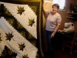Bussey, Louise.  Louise Bussey poses with her patchwork leaf quilt, St. Lunaire-Griquet.