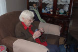 Simmonds, Mary Jane.  Mary Jane Simmonds knits in her living room, Conche, Newfoundland.
