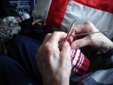 Simmonds, Mary Jane.  Close-up of Mary Jane Simmonds' hands while she knits, Conche, Newfoundland.