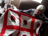 Simmonds, Mary Jane.  Mary Jane Simmonds holds up an applique apple quilt that she made, Conche,...
