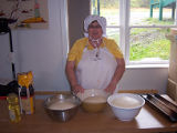Bread Making Workshop. A member of the French Shore Historical Society poses with rising dough, Conche,
