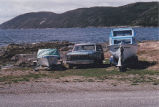 Two boats and a truck near the water, Conche, Newfoundland.