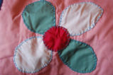 Carnell, Millie. Close-up of a flower patten applique quilt made by Millie Carnell, Flower's Cove.