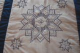 Carnell, Millie. Close-up of embroidered star pattern quilt made by Millie Carnell, Flower's Cove.