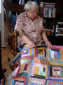 Elliott, Mary.  Mary Elliott poses with a 'mile-a-minute' quilt, Main Brook.