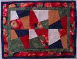 Pilgrim, Karen.  An apple themed quilted table mat made by Karen Pilgrim, Main Brook.