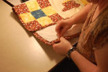 Main Brook Quilting Circle.  Wavey Pilgrim works on a quilted place mat, Main Brook.
