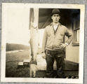 Unidentified man weighing a salmon
