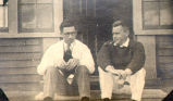 Two men sitting in front of the St. Anthony hospital