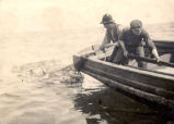 Two men in a boat hauling a cod bag