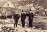 Three men standing near fishing sheds.