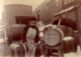 A cooper standing with a Job Brothers & Co. No. 1 Herring barrel, March 1903.
